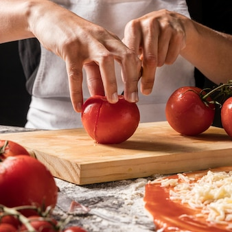 Close-uphanden die tomaat snijden