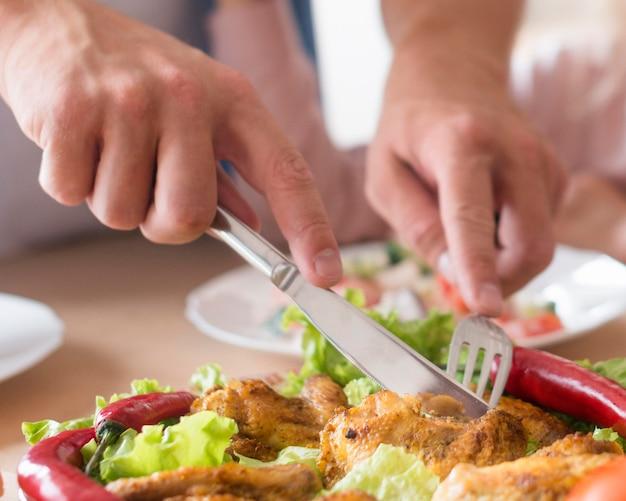 Close-uphanden die vlees snijden