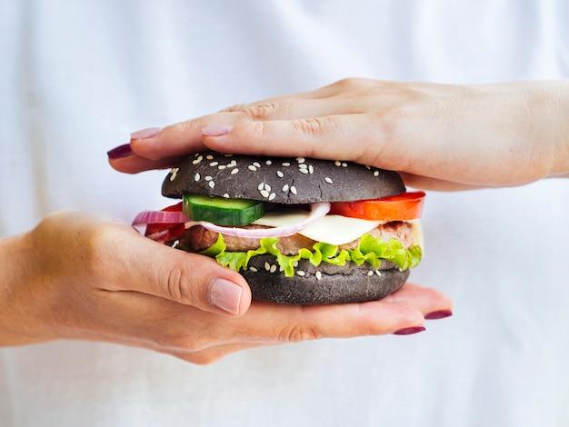 Close-uphanden die zorgvuldig hamburger houden