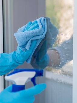 Close-uphanden met rubberhandschoenen die het venster schoonmaken