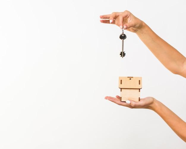 Close-uphanden met sleutel en een plattelandshuisje