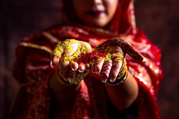Close-uphanden van het meisje die van india kleurrijk poeder in handen houden bij holifestival