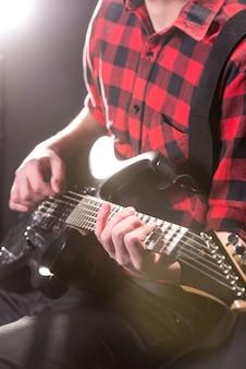 Close-uphanden van jonge gitarist met de elektrische gitaar.