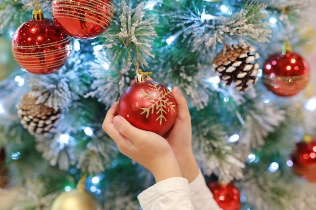 Close-uphanden van kinderen die kerstmisbal van kerstmisboom in de wintertijd en gelukkig nieuw jaar houden.