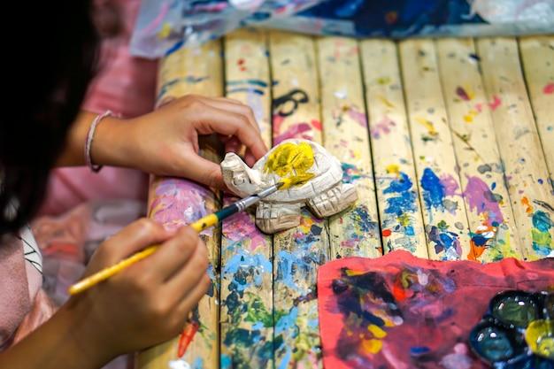 Close-uphanden van kunststudenten die verfborstelstudie houden en verf op houten dierlijke pop in het kunstklaslokaal leren.