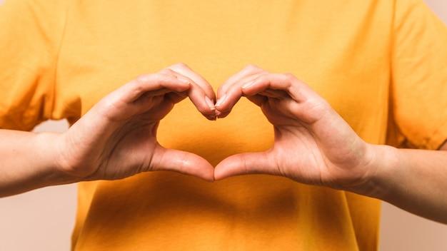 Close-uphanden van vrouw in vorm van hart. eigenliefde en welvaart