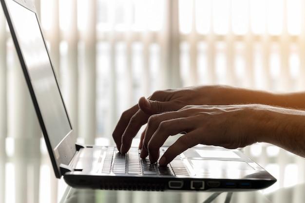 Close-uphanden van zakenlieden gebruiken laptops in het bureau.