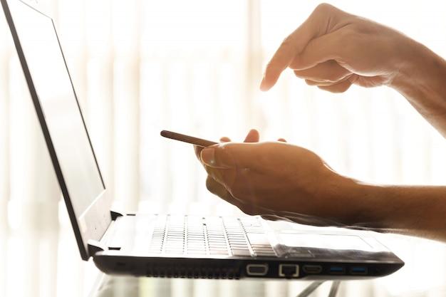 Close-uphanden van zakenlieden gebruiken smartphones en laptops op het kantoor.