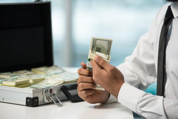 Close-uphanden van zakenman met kofferhoogtepunt van geld.