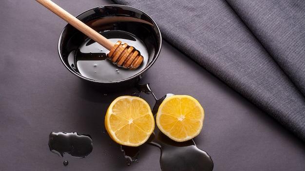 Close-uphoningstok en citroenplakken