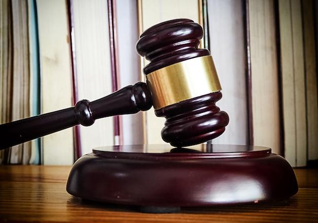 Close-uphoofd van rechtershamer gezet op houten bureau, voor vage gestapelde boeken, teken van rechtvaardigheid, wet