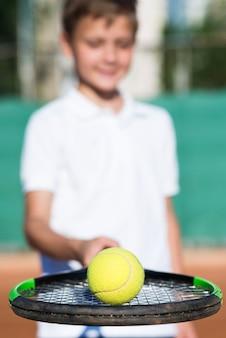 Close-upjong geitje dat een bal op de racket houdt