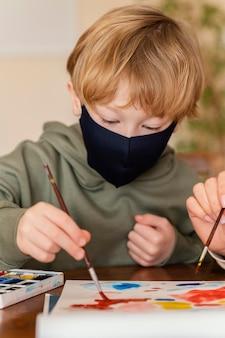 Close-upjong geitje met masker het schilderen