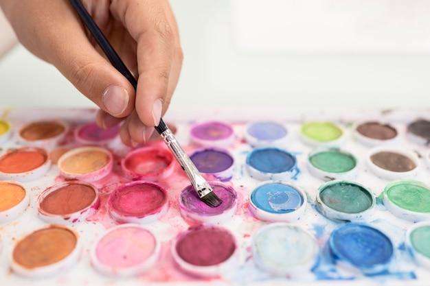 Close-upjongen die aquarelle thuis gebruiken