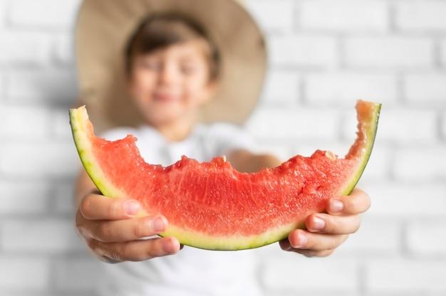 Close-upjongen die met hoed van watermeloen genieten