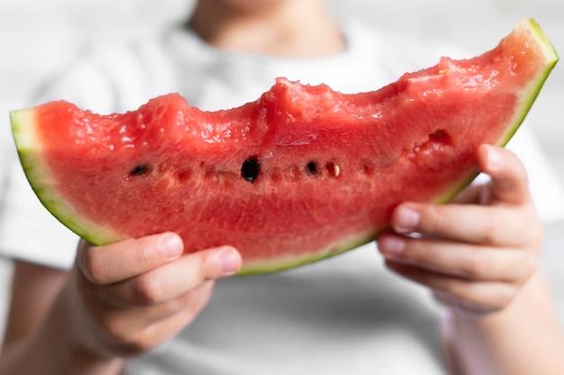 Close-upjongen die watermeloen eten