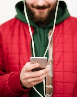 Close-upkerel met baard en smartphone