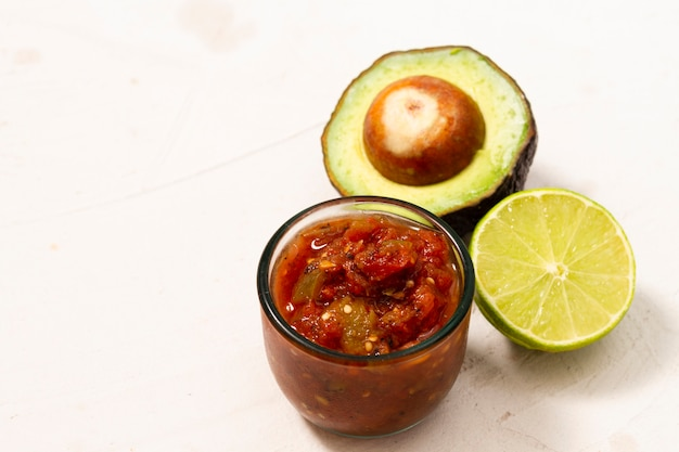 Close-upkom saus dichtbij avocado en kalk