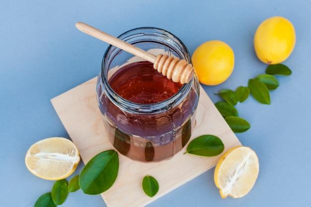 Close-upkruik met honing door citroenen wordt omringd die