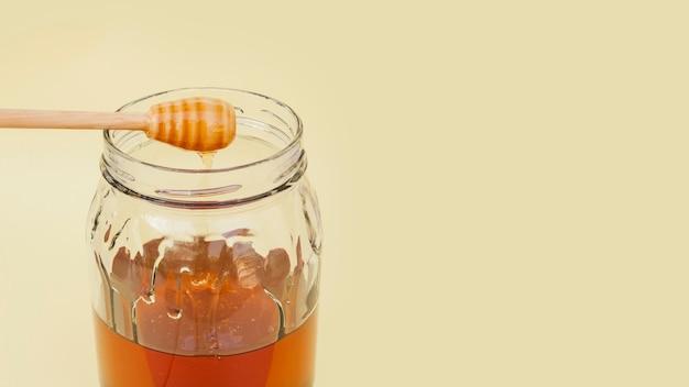 Close-upkruik met smakelijke honing wordt gevuld die