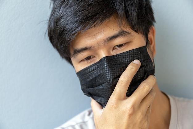 Close-upmannen die een masker dragen om coronavirus (covit-19) met zachte nadruk te beschermen