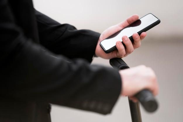 Close-upmannetje die autoped met mobiele telefoon gebruiken