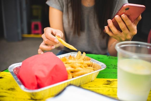 Close-upmeisje die met telefoon frieten eten