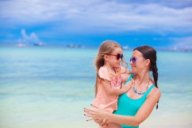 Close-upmeisje en haar jonge moeder die elkaar het strand bekijken