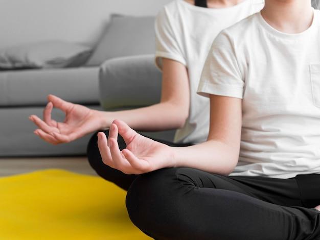 Close-upmeisje en mamma die yoga doen