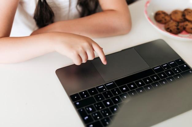 Close-upmeisje met chocoladeschilferkoekjes en laptop