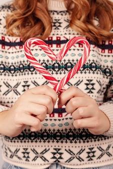 Close-upmeisje met het suikergoed van de sweaterholding