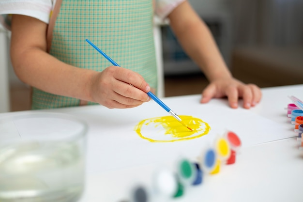 Close-upmeisje met schort het schilderen