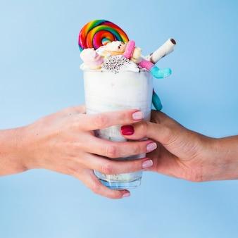 Close-upmening die van handen heerlijke milkshake houden