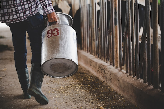 Close-upmening over de benen van landbouwer die met hooi bij de dierlijke schuur werken