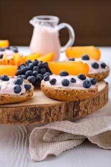 Close-upmening van broodjes met gestremde melk, bosbes en plak van dadelpruim