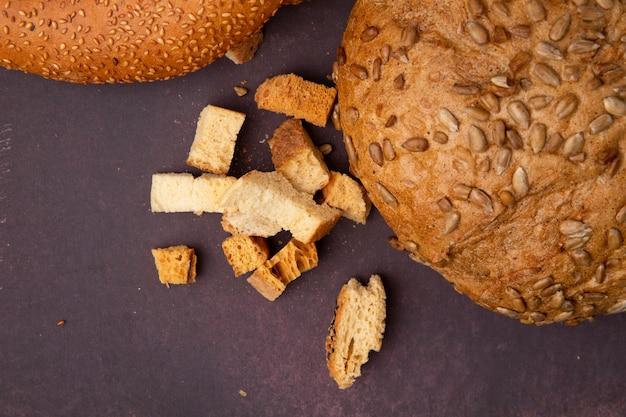 Close-upmening van broodstukken en bruine gezaaide maïskolf op maronachtergrond met exemplaarruimte