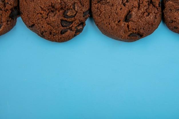 Close-upmening van de bloemloze koekjes van de pindakaasbrownie op blauwe achtergrond met exemplaarruimte
