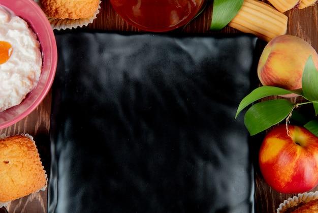 Close-upmening van de jam cupcake kaas van de perzikperzik perzik met plaat op centrum op houten lijst