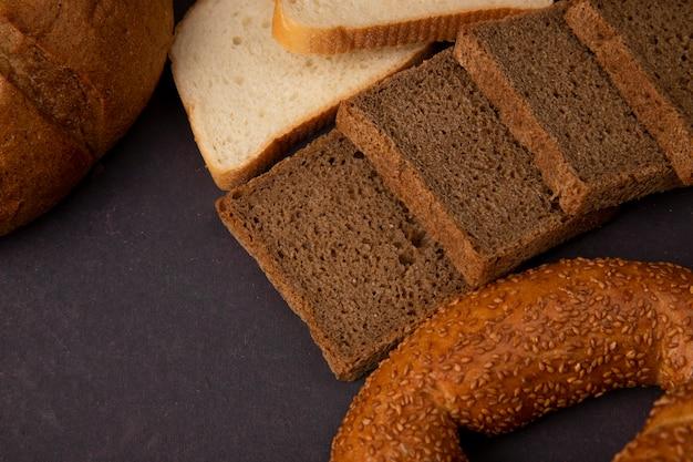 Close-upmening van de plakken van het roggebrood met de witte maïskolf en het bagel van broodplakken op kastanjebruine achtergrond met exemplaarruimte