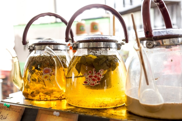 Close-upmening van drie glaspotten met verse groene thee