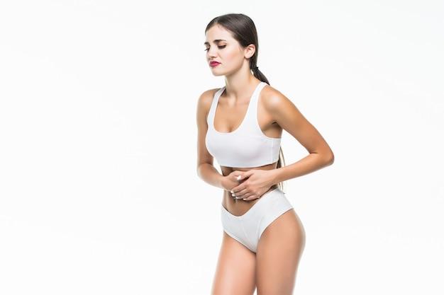 Close-upmening van een jonge vrouw met maagpijn of spijsvertering of periodecyclus op witte muur.