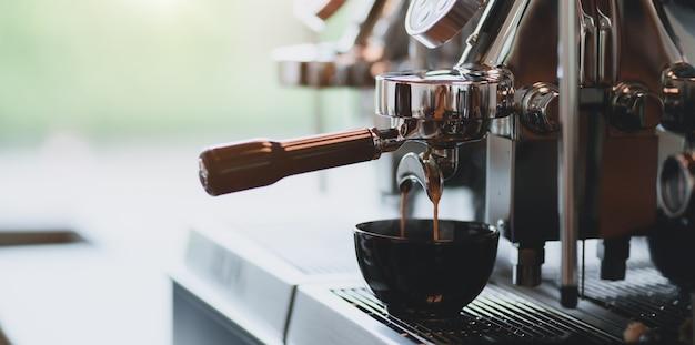 Close-upmening van espresso het gieten van espressomachine in een koffiekop