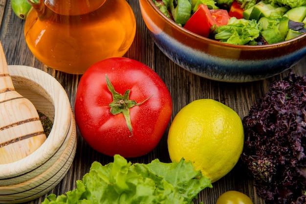 Close-upmening van groenten als basilicum van de tomatensla met plantaardige saladezwarte peper in knoflookmaalmachine gesmolten olie op houten lijst