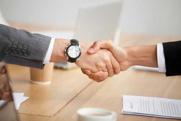 Close-upmening van handdruk, twee zakenlieden in kostuums die handen schudden