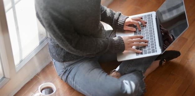 Close-upmening van het jonge vrouwelijke freelancer typen op laptop computer terwijl het zitten naast de vensters