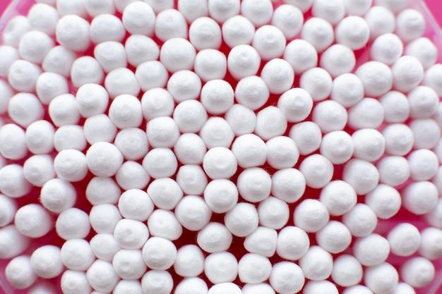 Close-upmening van hierboven op rond pak katoenen knoppen op roze achtergrond