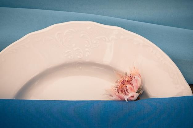 Close-upmening van huwelijk of andere gerichte gebeurtenislijst die, bloem, witte plaat, blauw servet, gebeurtenisdecoratie plaatsen
