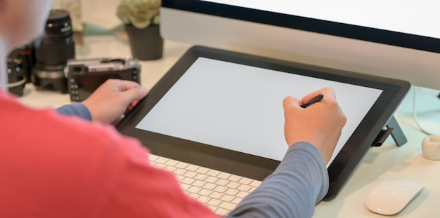 Close-upmening van jonge mannelijke fotograaf die zijn beelden op digitale tablet retoucheren