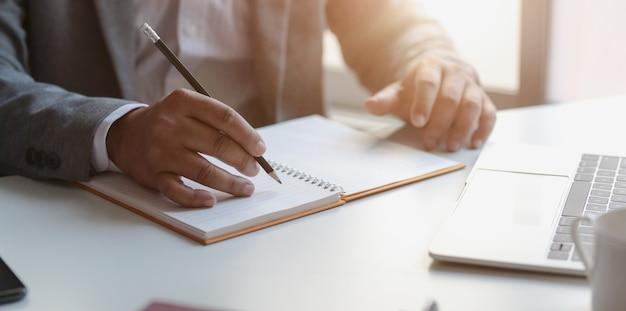 Close-upmening van jonge professionele zakenman die zijn ideeconcepten op notitieboekje schrijven