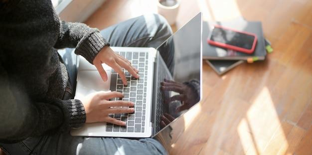Close-upmening van jonge vrouwelijke freelancer die aan haar project met laptop computer werken